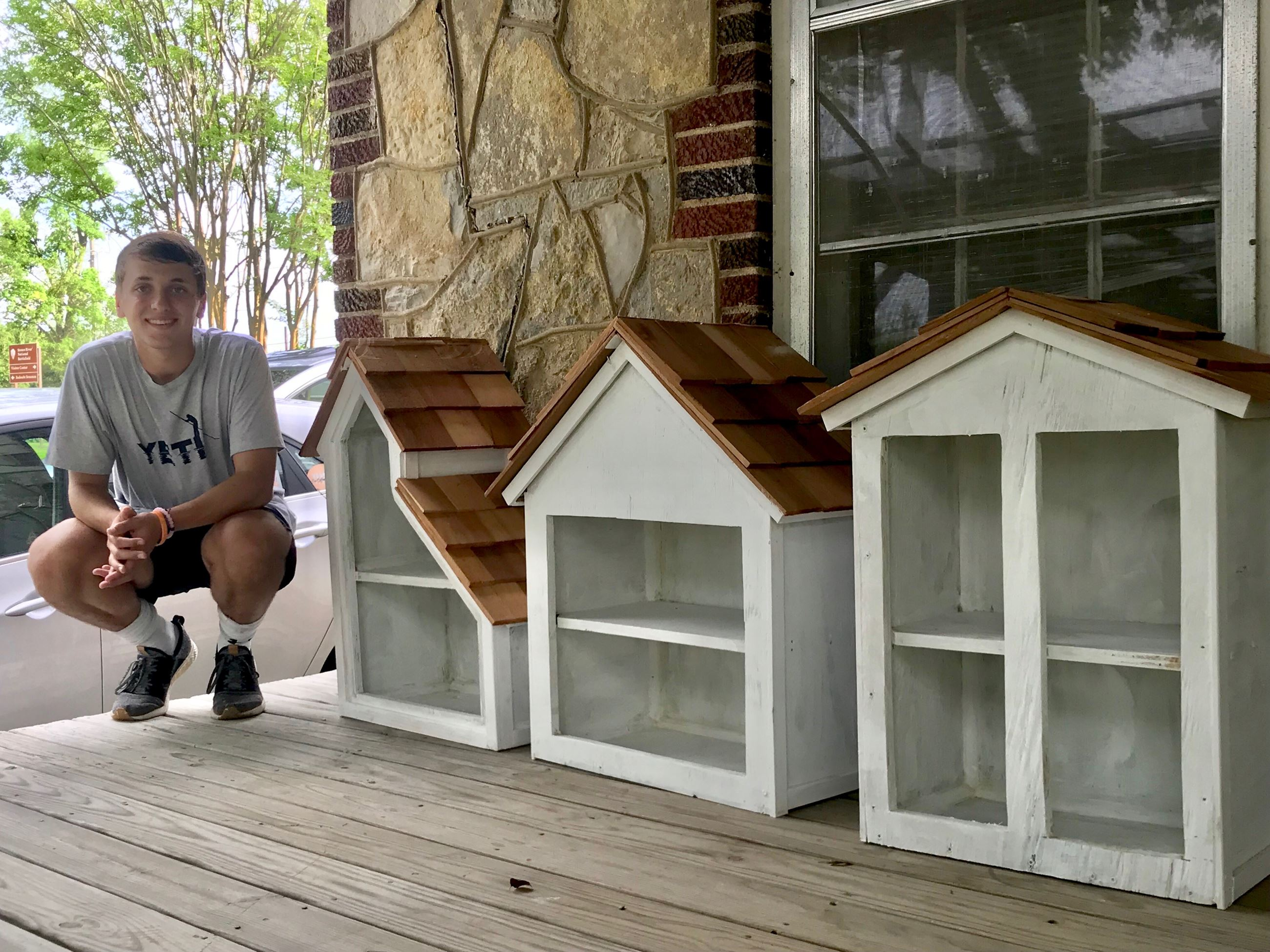 Eagle Scout poses with Little book lending Libraries he built for Eagle Project for MPRD