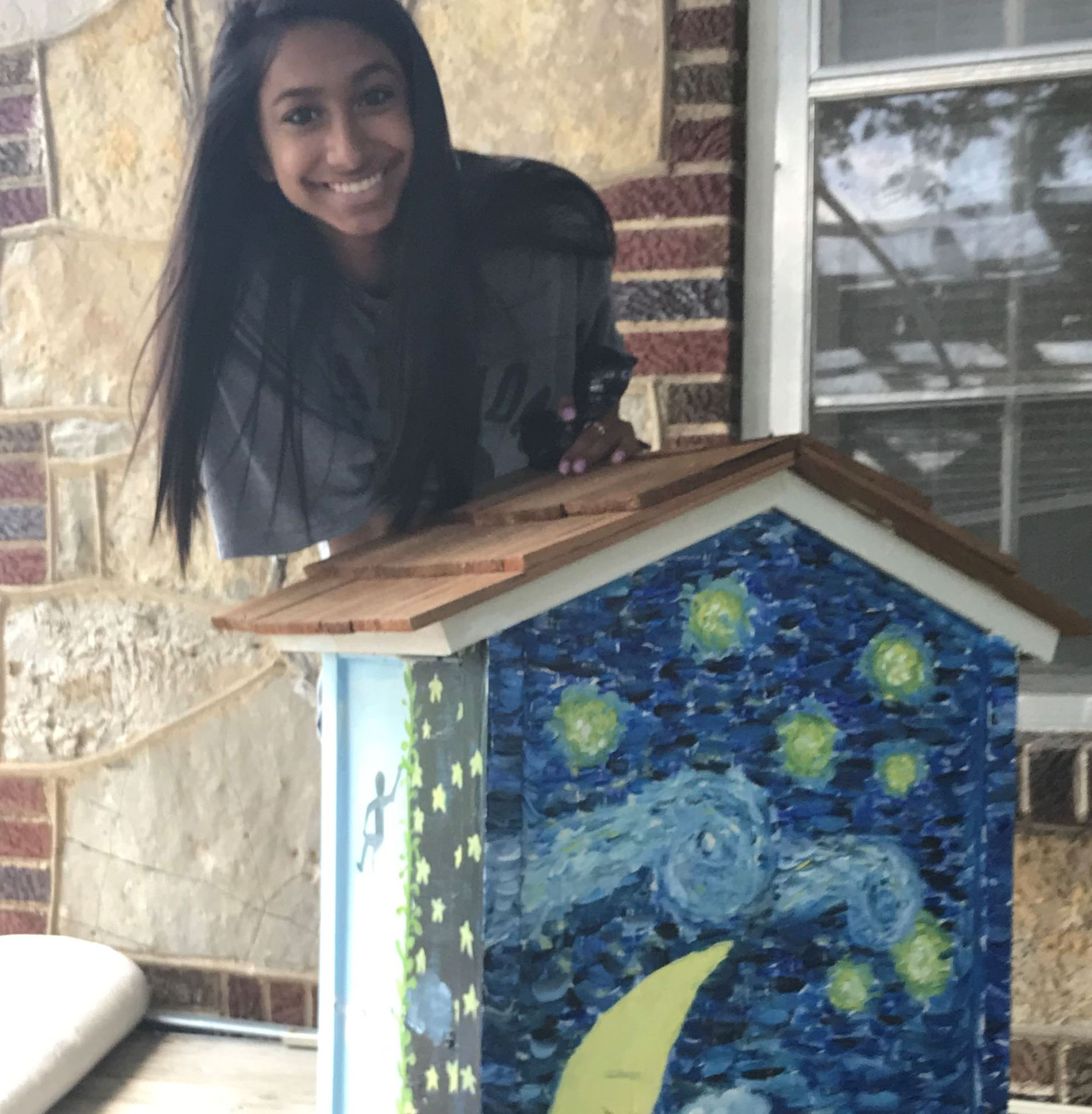 student posing with little book lending library she painted