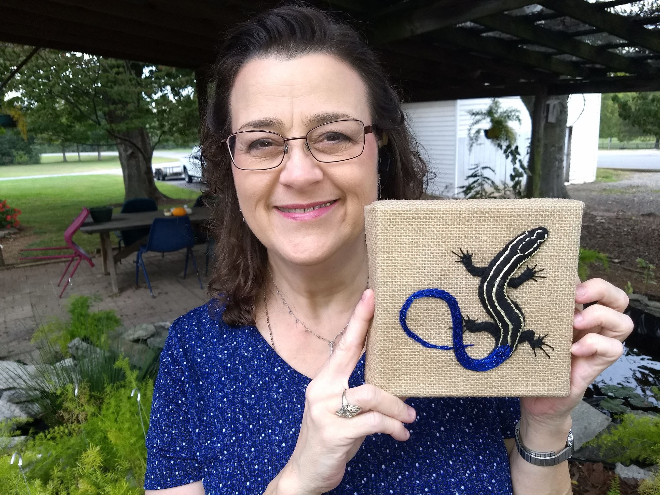 Amy Campbell holding embroidery piece of 5 lined Skink she created