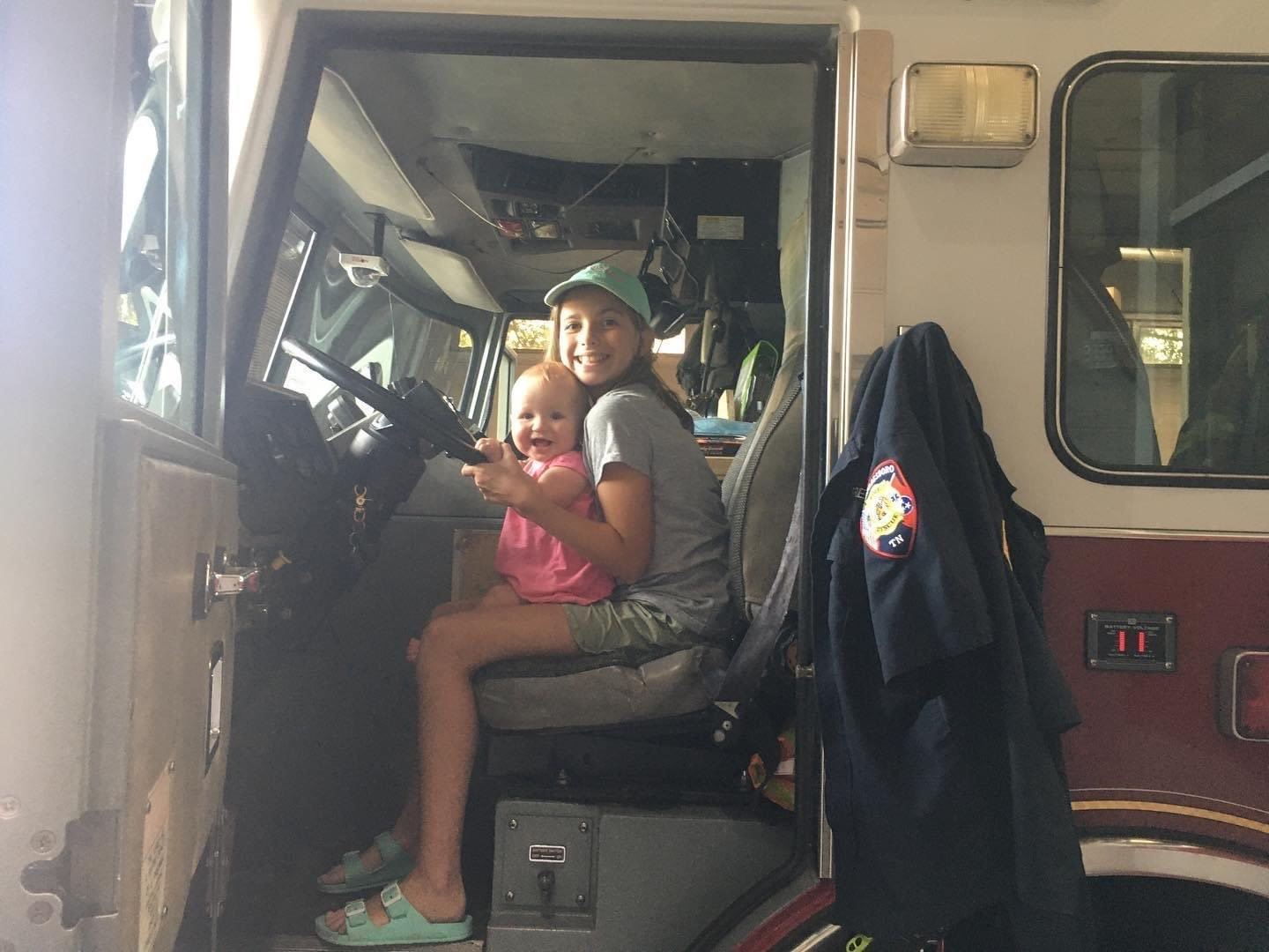 Little Girl and Baby sitting in Fire Truck