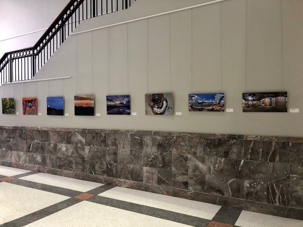 Row of Tom Womack Photos hung in Rotunda