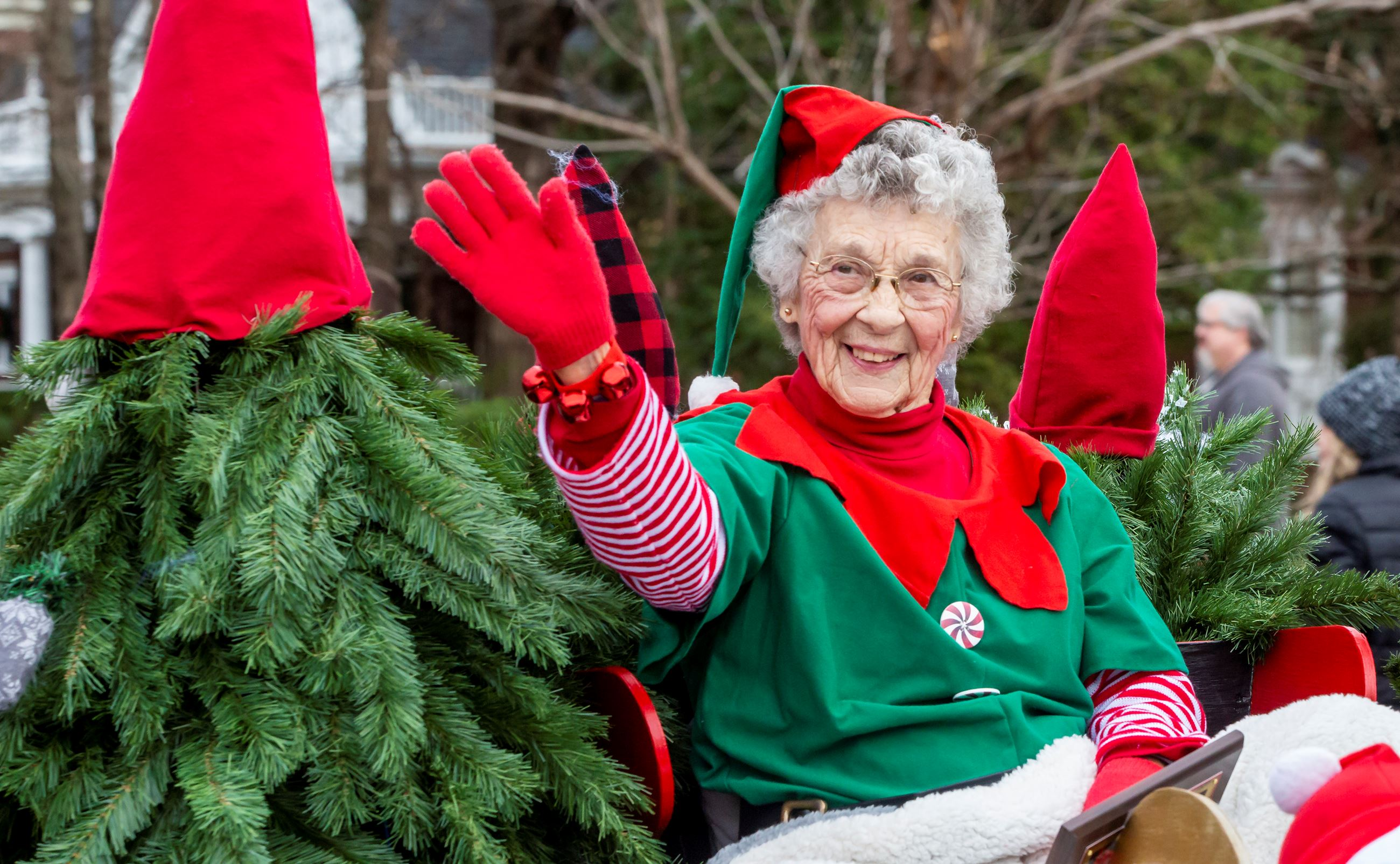 Woman with white hair wearing red and green elf outfit waving