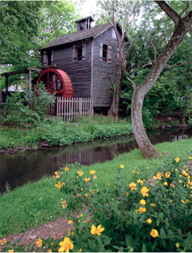 Historic gristmill with red waterwheel, creek, trees, lawn, & flowers